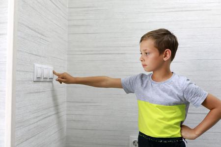 El niño apaga la luz en casa