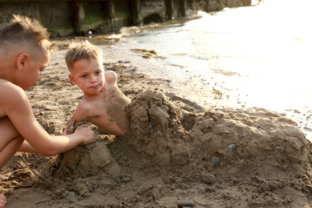 Boy burying his brother in sand on beach of the Sea of ??Azov