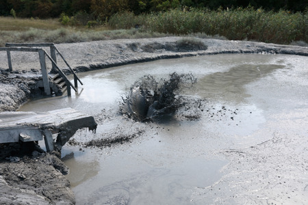 Person sliding on wooden mud hill into swamp Фото со стока