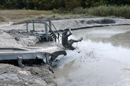 Man sliding on wooden mud hill into swamp Фото со стока