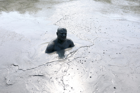 Portrait of mud man in a pond