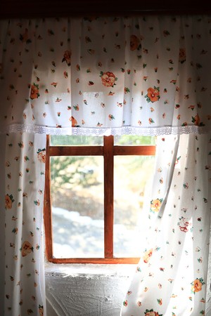 View of floral curtains in rustic hut Reklamní fotografie
