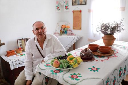 Senior man in dining room in village hut