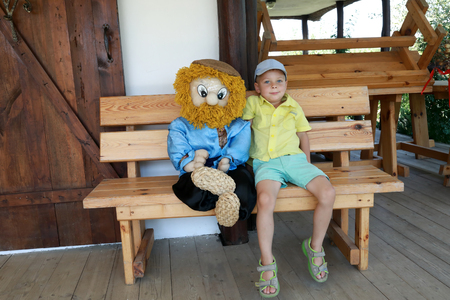 Boy sitting with toy goblin on wooden bench 写真素材