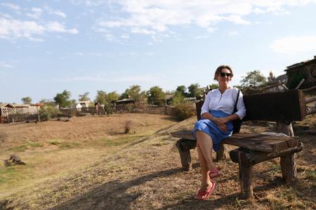 Woman sitting on wooden bench in village Reklamní fotografie