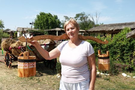 Elderly woman holding wooden yoke with buckets in village Stock Photo