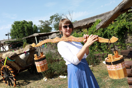 Woman holding wooden yoke with buckets in village