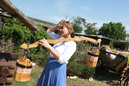 Tired woman holding wooden yoke with buckets