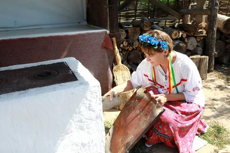 Woman lights fire in stove in backyard