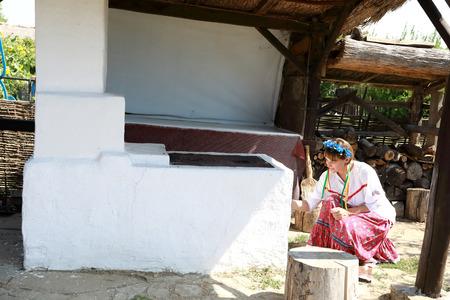 Cossack woman lights fire in russian stove in backyard 写真素材
