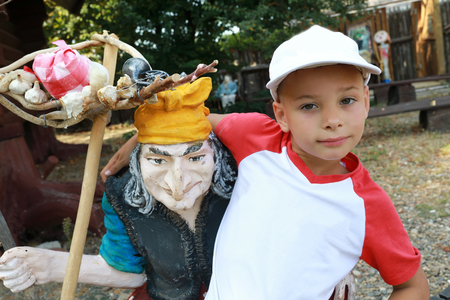 Child posing with Baba Yaga in park