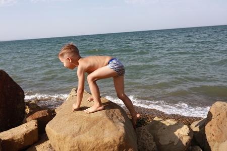 Child climbing on stone against Black Sea Stock fotó