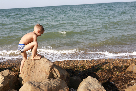 Boy climbing on stone against Black Sea