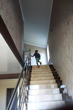 Child is climbing stairway of dwelling house