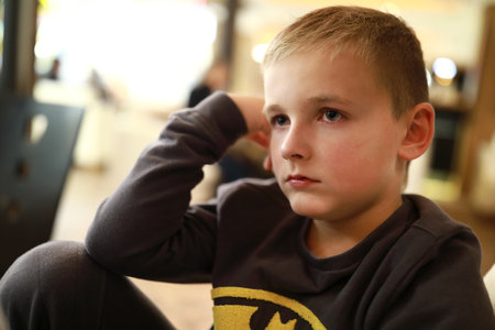 Portrait of pensive child sitting at home Reklamní fotografie