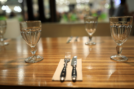 Wooden dining table with cutlery in restaurant