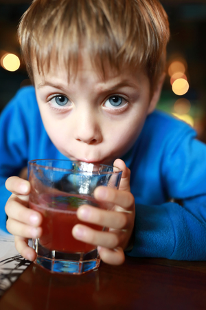 Kid has fruit drink in a restaurant
