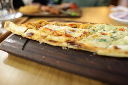 Sebzeli Pide Dish on wooden board in restaurant Stock Photo - 133842606