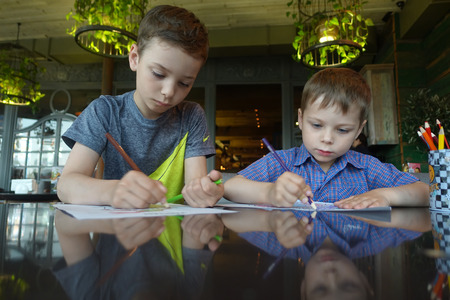 Two brothers drawing with pencil in a cafe Stock Photo