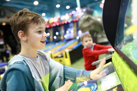 Boys playing arcade game in amusement park