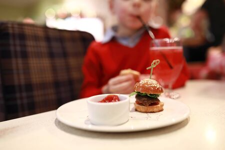 Mini burger and ketchup on plate in restaurant