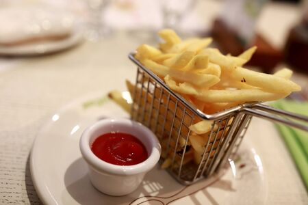 Plate with french fries and ketchup in restaurant