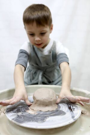 Child working at pottery wheel in a workshop