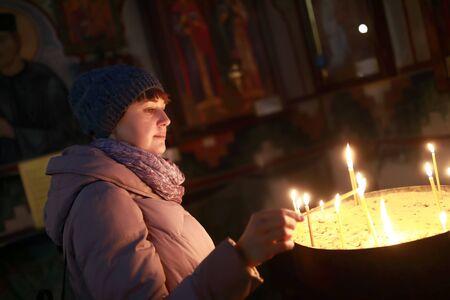 Woman lights candle in Georgian Orthodox church Stock Photo