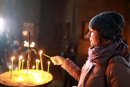 Woman lighting candle in Georgian Orthodox church Stock Photo