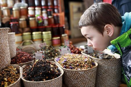 Boy sniffing herbal tea at the market