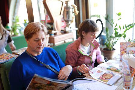 Two women choosing dishes in a restaurant 版權商用圖片
