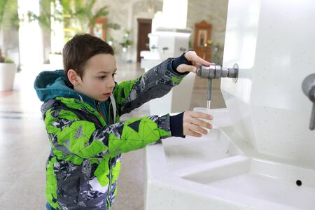 Child pouring water in drinking pump room, Kislovodsk, Russia