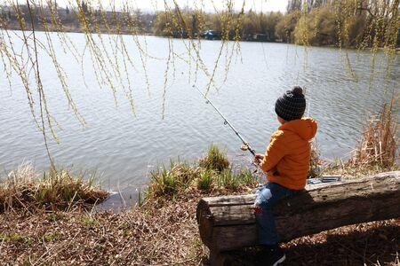 Kid fishing on lake in spring, Kislovodsk, Russia