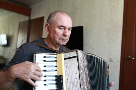 Serious man playing the accordion at home