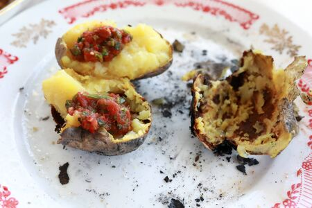 Plate with leftovers of charcoal baked potatoes on picnic Banque d'images