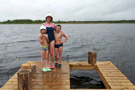 Mother with sons on wooden bridge after bath, lake Seliger