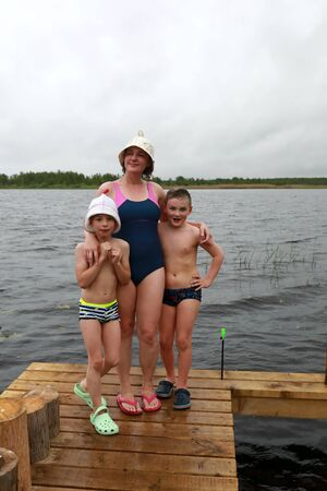 Mother with two sons on wooden bridge after bath, lake Seliger