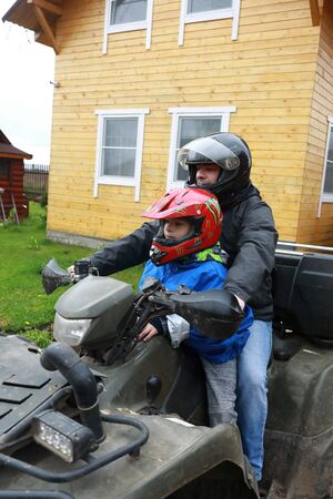 Portrait of father with son sitting on quad bike
