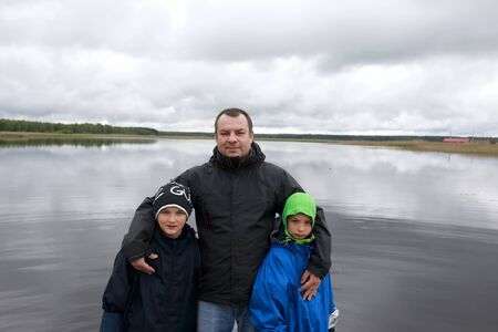 Portrait of father with sons on background of Lake Seliger