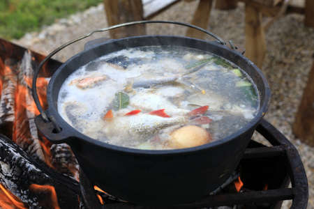 Cooking fish soup in cauldron on fire