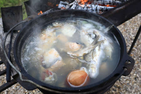 Cooked russian fish soup in cauldron on fire