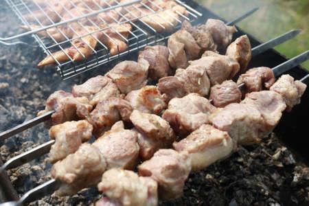 Cooking juicy pork neck on skewers in backyard