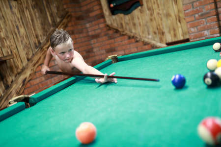 Portrait of child playing billiards at home Stok Fotoğraf