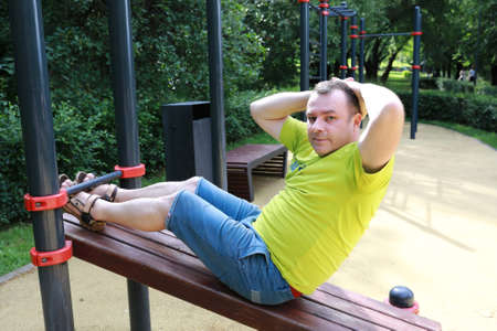 Man trains abdominal muscles on simulator in park