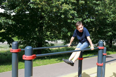 Boy trains abdominal muscles on uneven bars in park