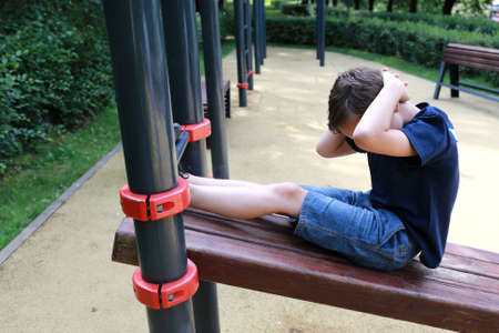 Child trains abdominal muscles on simulator in park