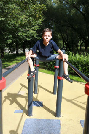 Child trains abdominal muscles on uneven bars in park