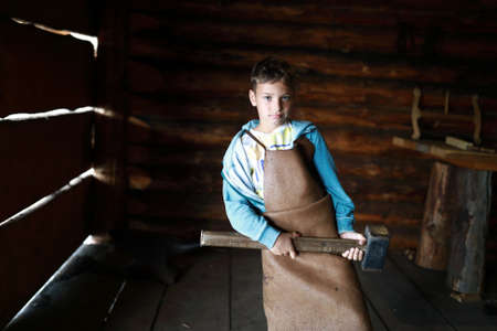 Portrait of kid holding hammer in forge Archivio Fotografico