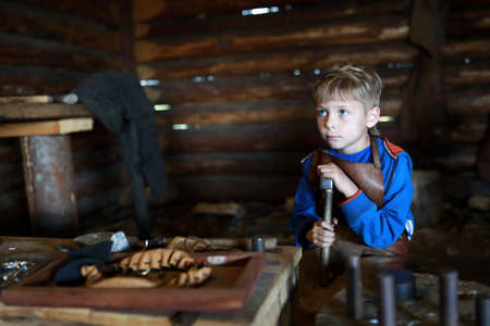 Portrait of child with hammer in forge