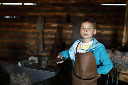 Portrait of boy with hammer in forge Archivio Fotografico